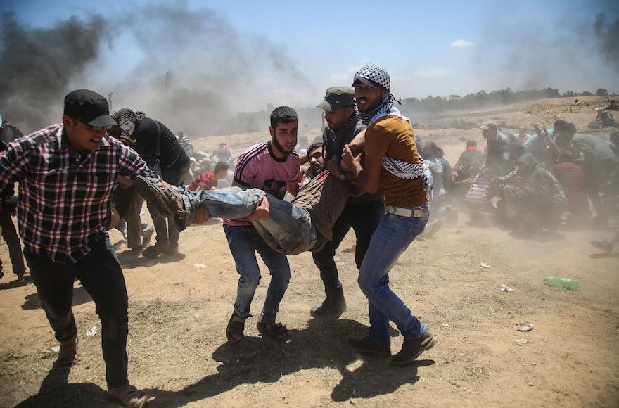 Palestinian Protests at Gaza Border Delayed as Funerals Take Place for at Least 58 Dead