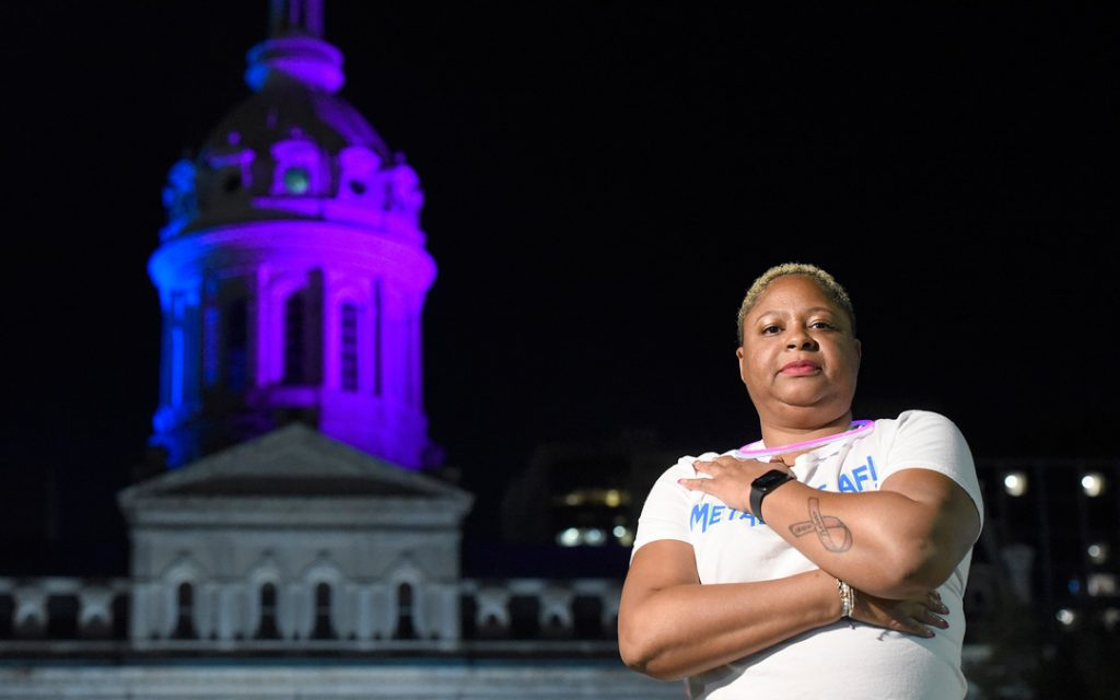 Chawnte Randall is shown in front of Baltimore's City Hall, which was recently lit up in honor of those living with metastatic breast cancer. (Photo by Steve Ruark)