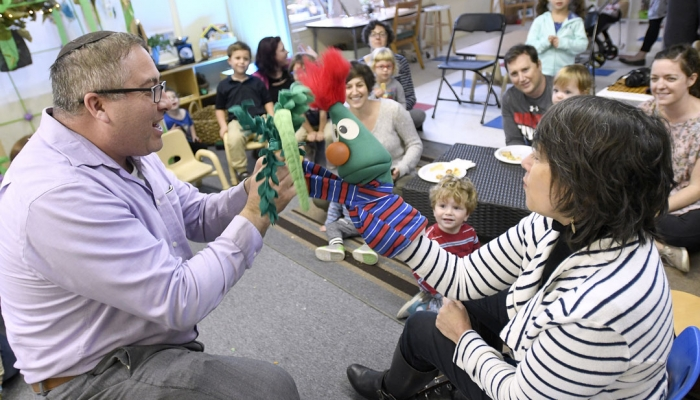 "Rabbi Etan Mintz, left, and music teacher Becky Gordon, right, lead a program during the ""Sukkot Under the Stars"" event at Beth El preschool in Federal Hill. (Photo by Steve Ruark)"