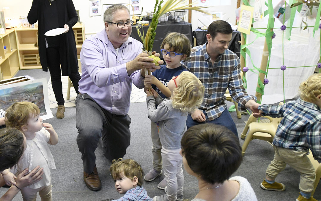 "Rabbi Etan Mintz helps children shake lulov and etrog during the ""Sukkot Under the Stars"" event at Beth El preschool in Federal Hill. (Photo by Steve Ruark)"