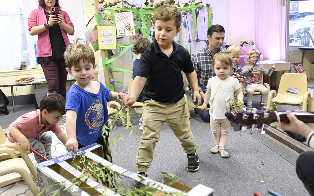 "Brothers Shai, left, 3, and Noam Neft, center, 5, place sechach on the roof of a small sukkah during the ""Sukkot Under the Stars"" event at Beth El preschool in Federal Hill. (Photo by Steve Ruark)"
