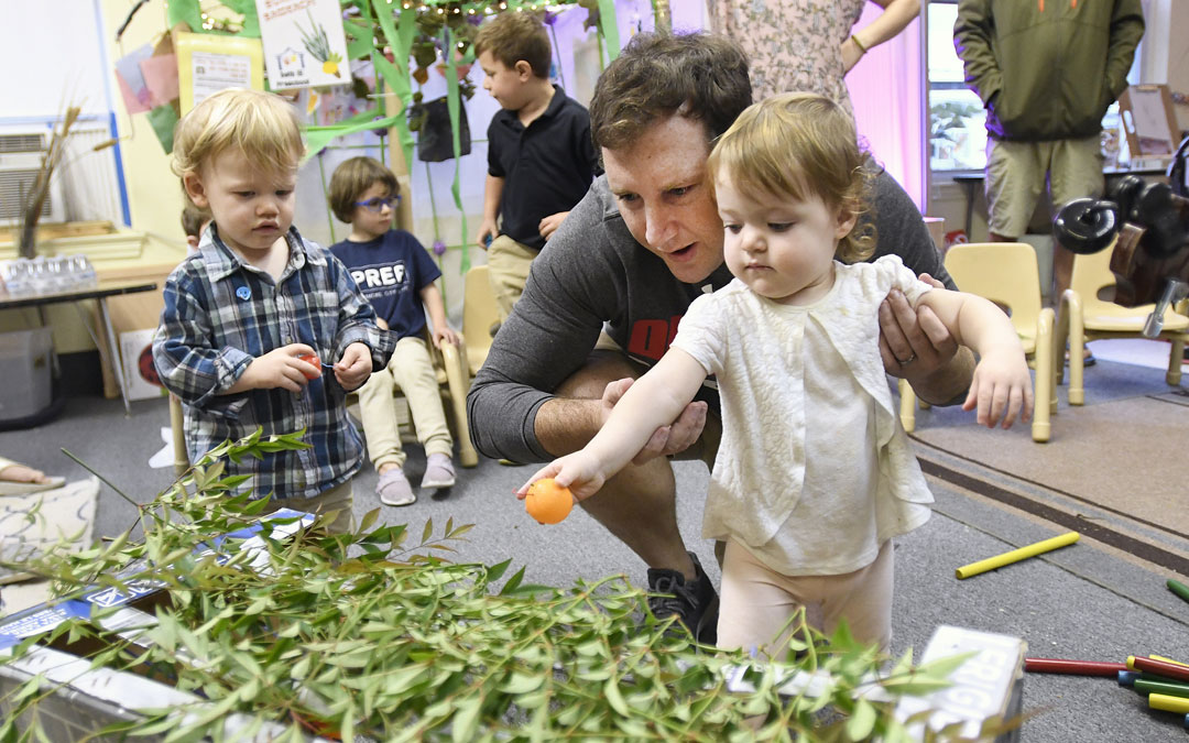 "Mike Rubin helps his 18-month-old daughter Ida place citrus in a small sukkah during the ""Sukkot Under the Stars"" event at Beth El preschool in Federal Hill. (Photo by Steve Ruark)"