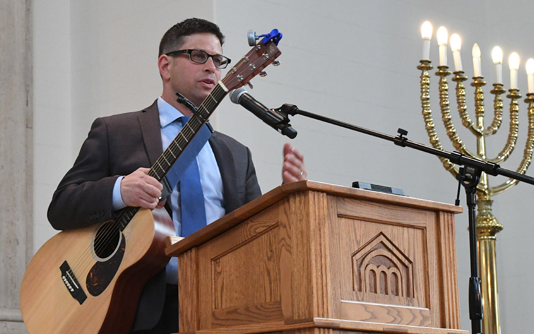 Rabbi Daniel Cotzin Burg talks to the Beth Am audience before playing his guitar. (Photo by Jim Burger)