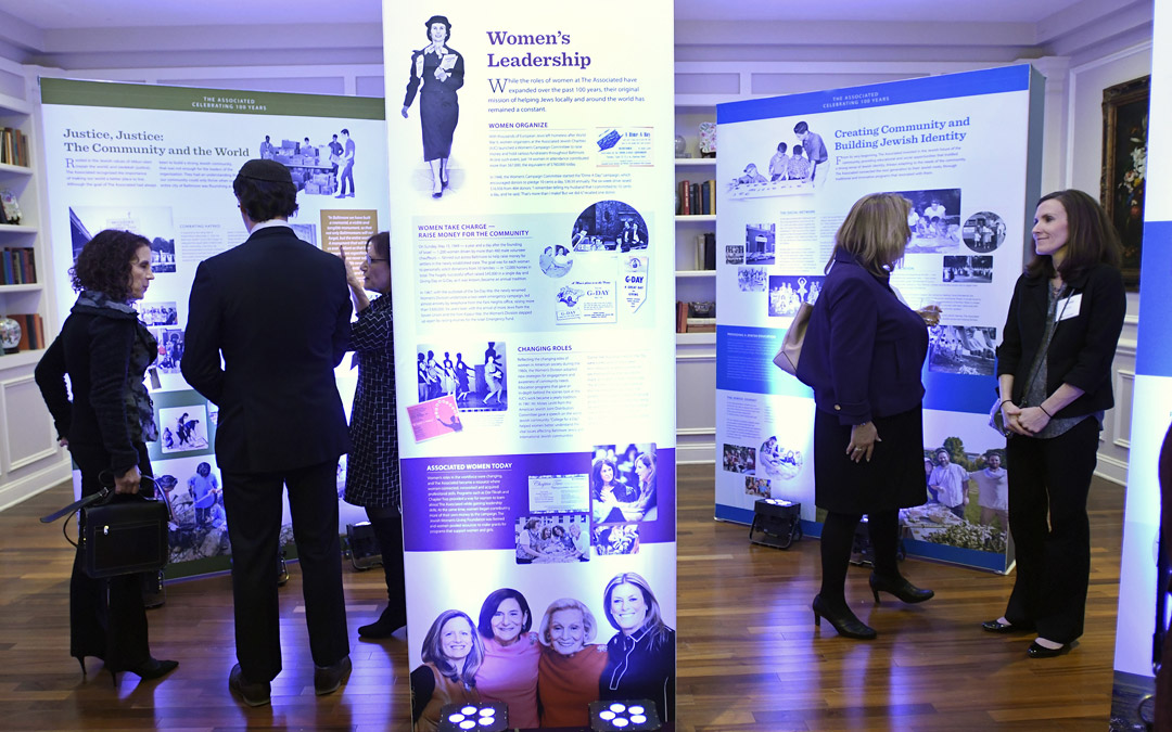 Guests mingle near a display about The Associated's history during the organization's kickoff for its Centennial Campaign. (Photo by Steve Ruark)