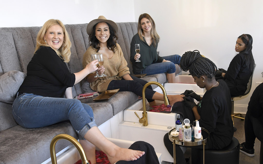 "From left, Kirsten Johnsen, Ariel Lewis, and Jenn George receive pedicures during a ""Galentine's Day"" outing at Self.ish Beauty in Pikesville. (Photo by Steve Ruark)"