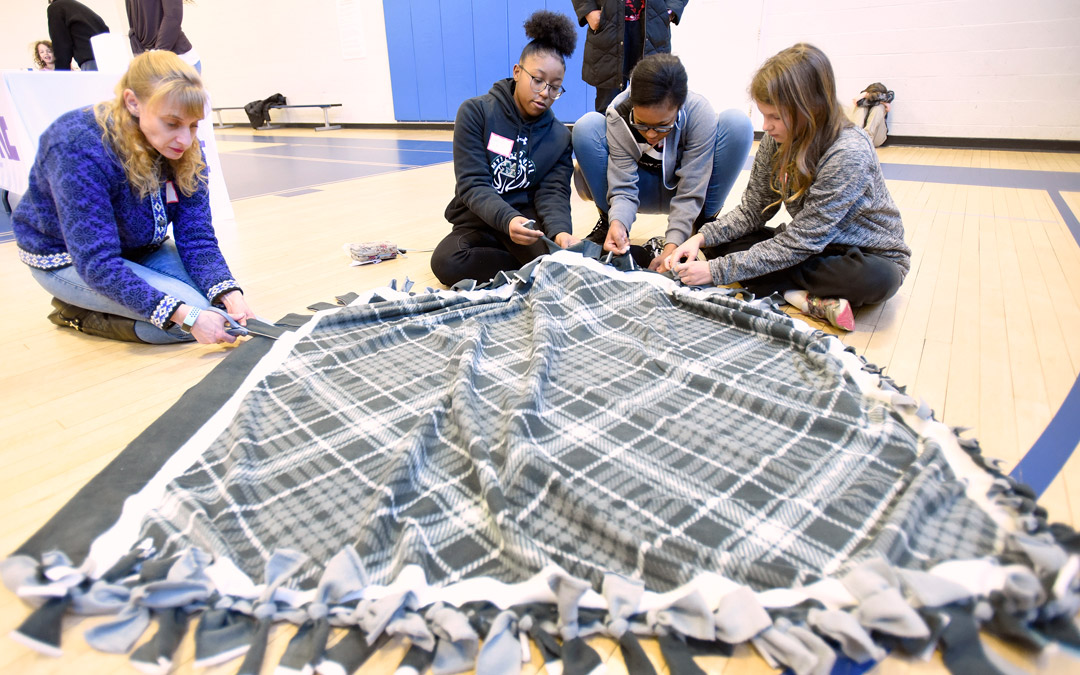 Volunteers, from left, Yael Goldwater, of North Laurel, Alexis Perry, 15, of Pikesville, her sister Amaya Perry, 14, and Emma West, 12, of Cockeysville, make a fleece blanket for INNterim House during Jewish Volunteer Connection's Martin Luther King Day Jr. Day of Service program at the Weinberg Park Heights Jewish Community Center. (Photo by Steve Ruark)