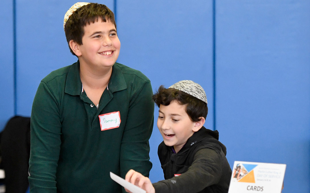 Ohr Chadash Academy fifth-graders Sammy Carter, left, and Yair Sebbag, both 11, man a table for making cards to be included in kindness kits for volunteers during Jewish Volunteer Connection's Martin Luther King Day Jr. Day of Service program at the Weinberg Park Heights Jewish Community Center. Fifth-graders from Ohr Chadash served as leaders at many of the program's volunteer stations. (Photo by Steve Ruark)