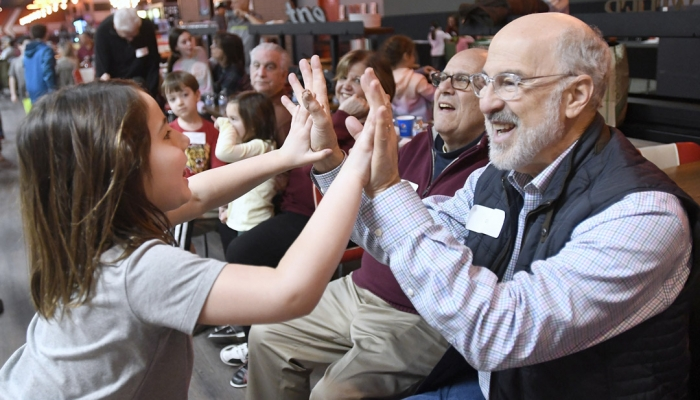 Gil Abramson, right, high-fives his granddaughter during the Macks Center for Jewish Education's Saba-ba: Grandparents on the Go launch party at AMF Pikesville Lanes (Photo by Steve Ruark)
