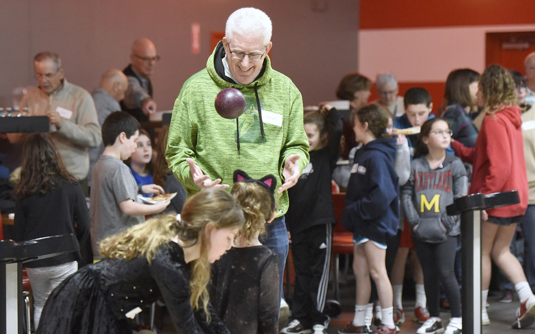 Richard Friedlander, of Pikesville, shows off for his granddaughter Anna Galiatsatos, 6, of Pikesville, during the Macks Center for Jewish Education's Saba-ba: Grandparents on the Go launch party at AMF Pikesville Lanes. The Saba-ba program brings together children and their grandparents. (Photo by Steve Ruark)