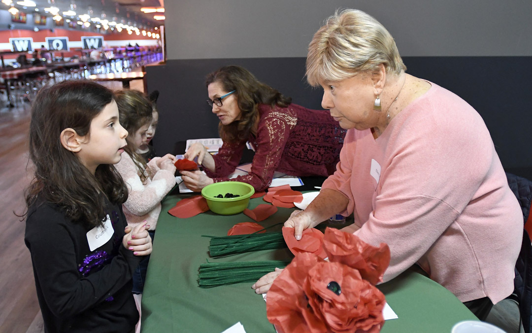 Ellen Stein, right, of Pikesville, helps Courtney King, left, 6, of Pikesville, make a poppy flower for Tu B'Shevat during the Macks Center for Jewish Education's Saba-ba: Grandparents on the Go launch party at AMF Pikesville Lanes. At center is Laura Stein, also of Pikesville. (Photo by Steve Ruark)