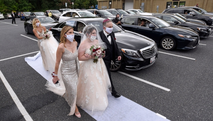In the parking lot of the Horizon Cinemas Fallston, the bride is walked down the aisle by her parents.