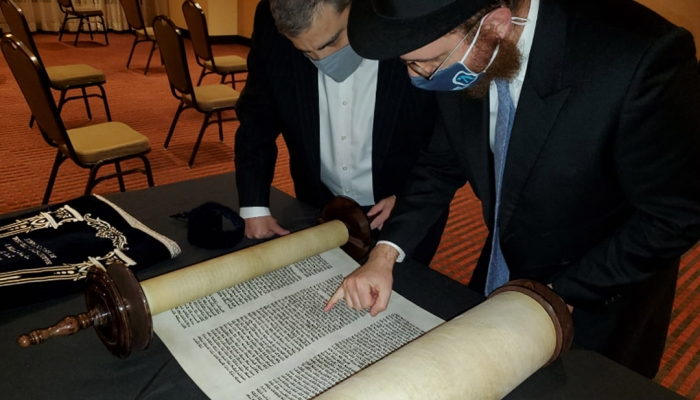 Rabbi Levi Druk (right) and Elton Juter inspect the new Torah. (Photo by Naftali Druk, Chabad of Downtown)