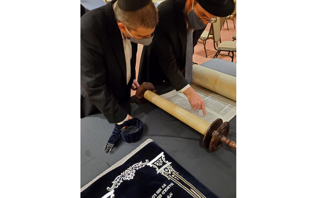 The new Harold Juter Torah is inspected carefully by Rabbi Levi Druk (right) and Elton Juter. (Photo by Naftali Druk, Chabad of Downtown)